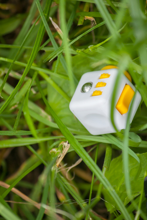 Yellow white cube antistress in grass, anti-stress cube is lost, Fidget Cube Simple Stress Reliever, Fingers Toy Stock Photo