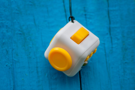 Cube anti-stress on a blue background, Fidget Cube Simple Stress Reliever, Fingers Toy
