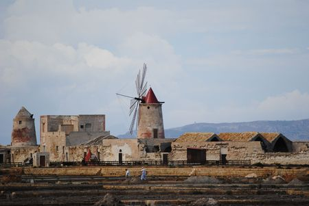 windmills in salt flats near Trapani in Sicily Stock Photo