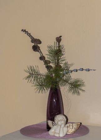 Christmas still life with fir green, a flower vase and an angel made of porcelain