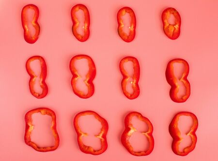 Red bell pepper cut pieces on pink background on pink background.