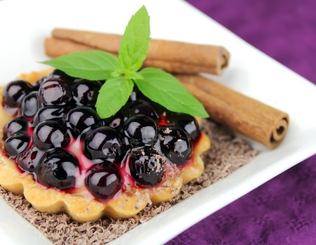 Pie with fresh berries, cinammon and mint on the white photo