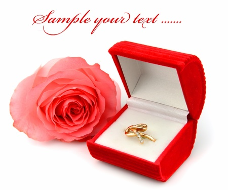 openly: Gift.The golden ring in a  red box and a rose flower on a white background.