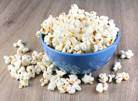 Tasty popcorn in the plate on wooden table photo