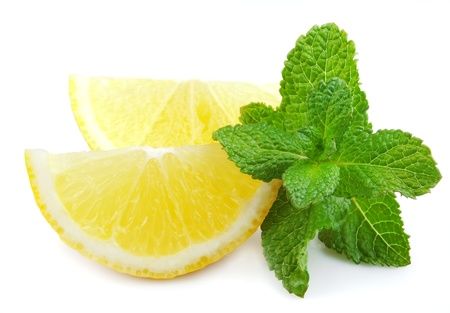 Segments of a lemon with fragrant mint on a white background photo