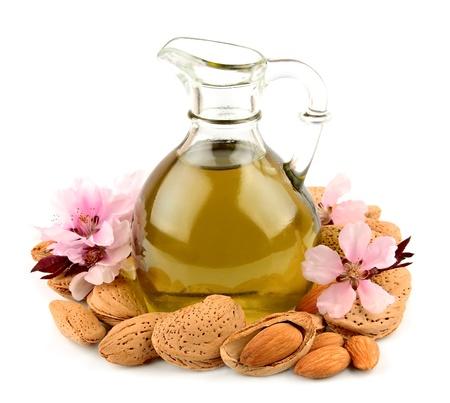 aceite de almendras y frutos secos de almendras con flores sobre fondo blanco Foto de archivo