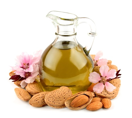 oil massage: almond oil and almond nuts with flowers on white background