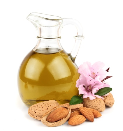 almond: almond oil and almond nuts with flowers on white background