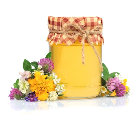 Honey in glass jars with flowers isolated on white  photo