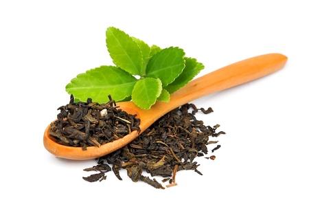 Thee bladeren en gedroogde thee op een houten lepel op wit