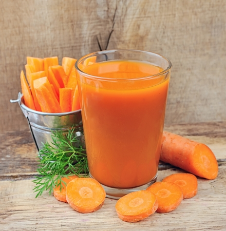 carrot juice: carrot juice and carrots segments on a wooden background