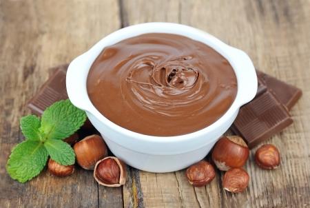 Hazelnut cream with hazelnut nuts and chocolate on wooden table Stock Photo - 18086771