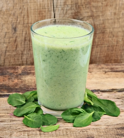 energy mix: Spinach smoothie with young leaves spinach on wooden tables
