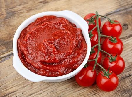 salsa de tomate: Pasta de tomate con tomates maduros en mesas de madera