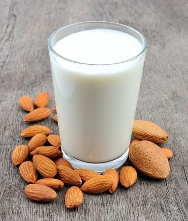 leche y derivados: Leche de almendras con almendras en una mesa de madera Foto de archivo