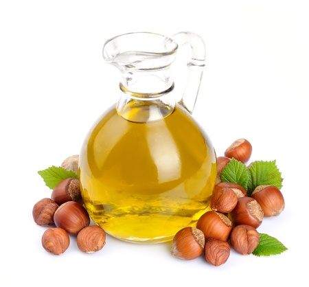 Hazelaar olie met hazelnoten noten close-up op wit Stockfoto
