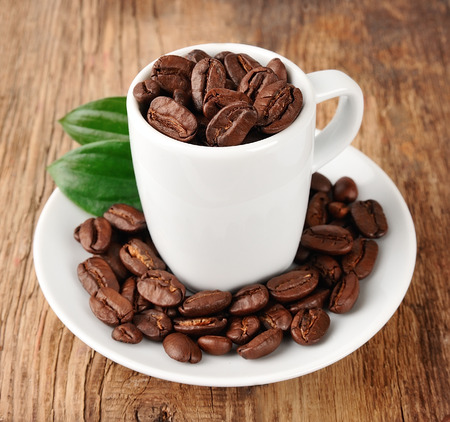 large bean: Coffee beans with leaf on wooden tables