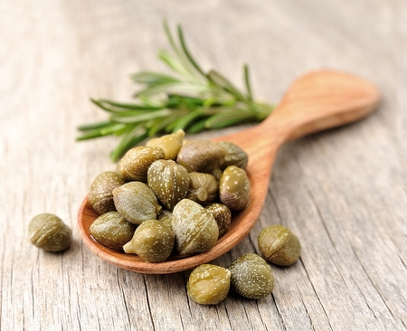 capers: Pikled capers on wooden texture. Stock Photo