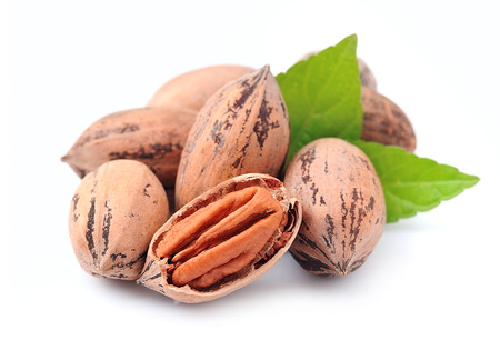 pecan: Pecan nuts with leaves close up on white background Stock Photo