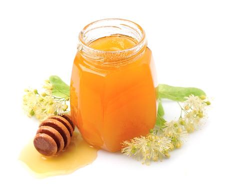 tilo: Miel con flores de tilo isolatewd en blanco. Foto de archivo