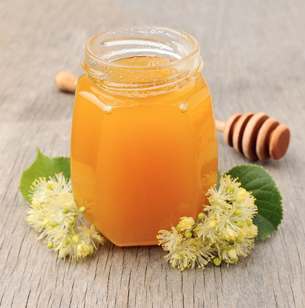 blossom honey: Honey with linden flowers on wooden texture.