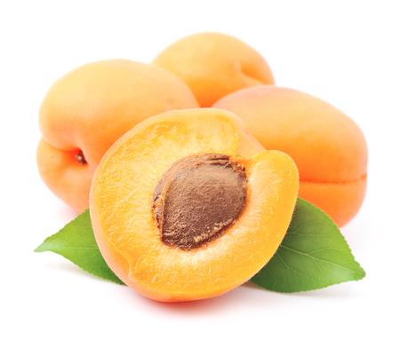 Zoete abrikozen vruchten met bladeren op wit Stockfoto