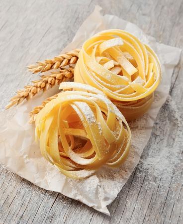 freshly prepared: Freshly prepared fettuccine pasta closeup. Pasta tagliatelle with wheat. Stock Photo