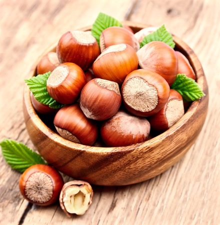filbert: Filbert nuts with leaf on wooden background .