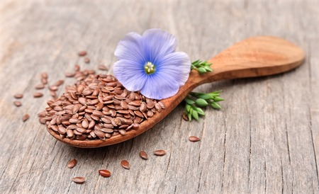 Flax seeds with flowers close up on wooden texture.