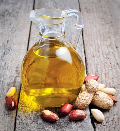 Peanut oil  with nuts on wooden tables closeup