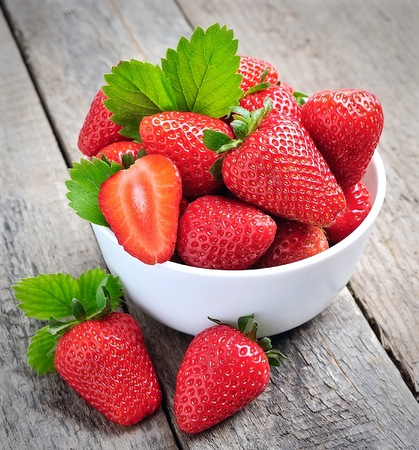 sweet and savoury: Ripe strawberry on the old wooden textured table Stock Photo