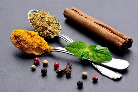 Especias aromáticas sobre fondo negro. Curcuma, canela, pimienta y especias de origano. Foto de archivo