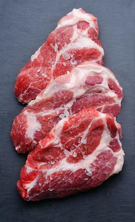 grafit: Crude meat on graphite board. Zdjęcie Seryjne