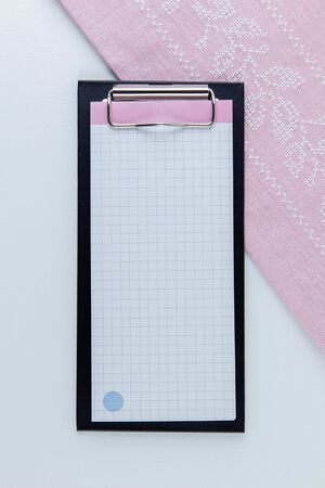 Notebook for notes on a white background. Nearby lies a pink napkin with embroidery.