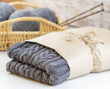 Handmade gray sweater is packed in kraft paper. Handmade knitted sweater. In the background is a wicker basket with knitting needles. Archivio Fotografico