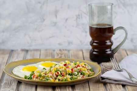 Rice with vegetables pepper, peas, corn and fried eggs on a plate. Place for text.