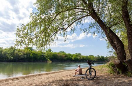 A cyclist resting on the banks of the Kuban River. A man is going to bathe in the river.