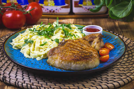 Grilled pork steak with bone in sweet honey glaze and pasta and fresh vegetables close-up on a plate on the table. horizontal Archivio Fotografico