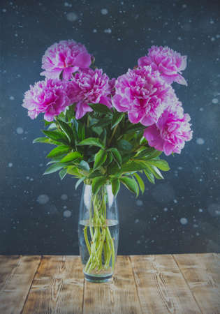 A bouquet of pink peonies stands in a vase. High quality photo