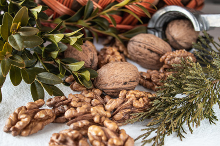 Walnuts and kernels of nuts on a white background near the basket.