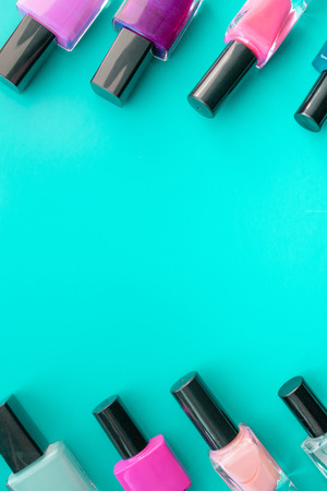 Bottles of nail polish. A group of bright nail polishes on a green background. With empty space in the middle. View from above
