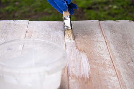 Man paints a white paint surface. Coloring boards. Painting wooden boards.