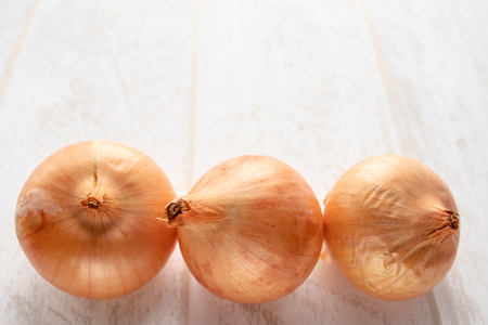 Fresh onions on wooden background. Vegetables for a healthy diet. Vegan food. Yellow onion 写真素材
