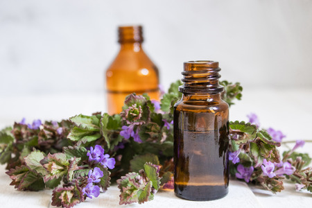 Essential aromatic oil with flowers on wooden background. Selective focus. Natural essential oil.