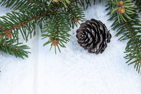 Green branches of a Christmas tree and cones on a white board background. Top view with copy space for your text.