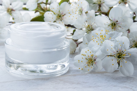 White can, cosmetic cream and cherry flowers on a white background. Face cream