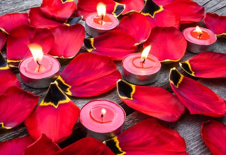 Fallen, red tulip petals near burning candles. A candle is burning near the tulip petals. Foto de archivo