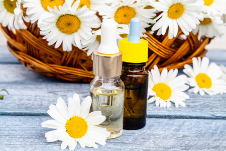 Chamomile essential oil in a glass bottle with a pipette stands on wooden boards near a basket with daisy flowers. Standard-Bild