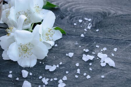 White jasmine flowers and green leaves lie on a wooden background. There is a place for your text. Copy space.