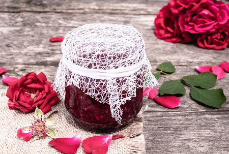 Jar of jam of rose petals on a wooden table with flowers of roses. Flower confiture. Healthy food. Copy space